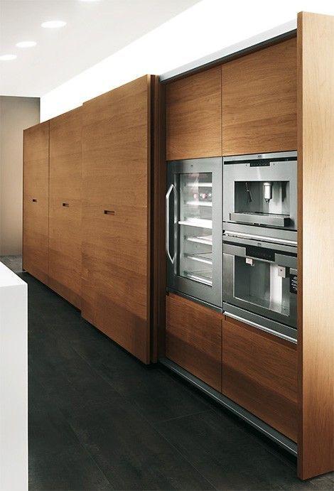 high end kitchen storage with wooden sliding door, pantry inside, dark grey floor, white wall, white sink