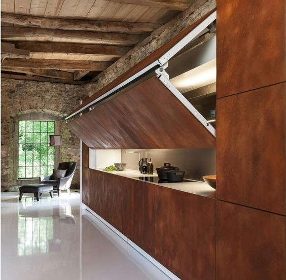 high end kitchen with brown wooden colored closing, white inside with LED lights, wooden beams, brown natural stones wall, white floor