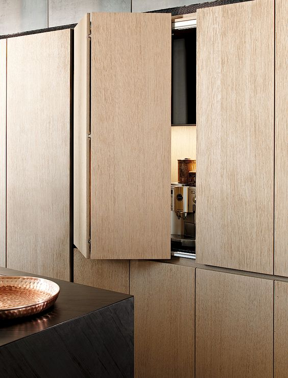 high end kitchen with light brown wooden fold door, black island