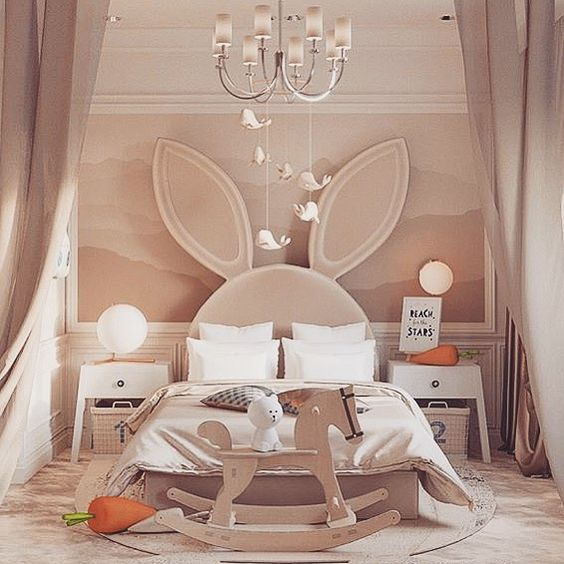 kids bedroom, pink wall, pink floor, pink rabbit headboard, white side table with rattan basket, chandelier, dolphin accessories, hore toy