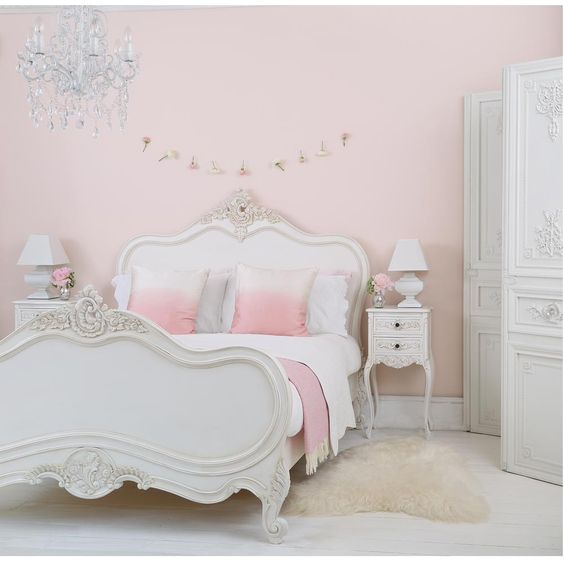kids bedroom, white wooden floor, pink wall, white wooden bed platform with details, crystal chandelier, white side table, white table lamp