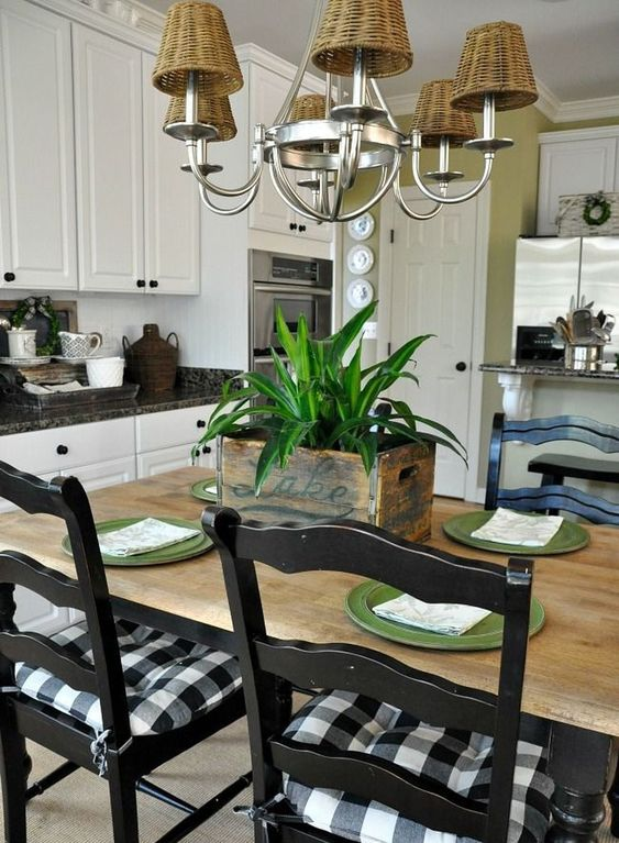 kitchen, brown floor, wooden dining set with black chairs, white upper and bottom cabinet, rattan chandelier
