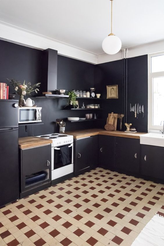 kitchen, brown plaid floor, black wall, black refrigerator, black bottom cabinet wooden top, black floating shelves, white bulb pendant