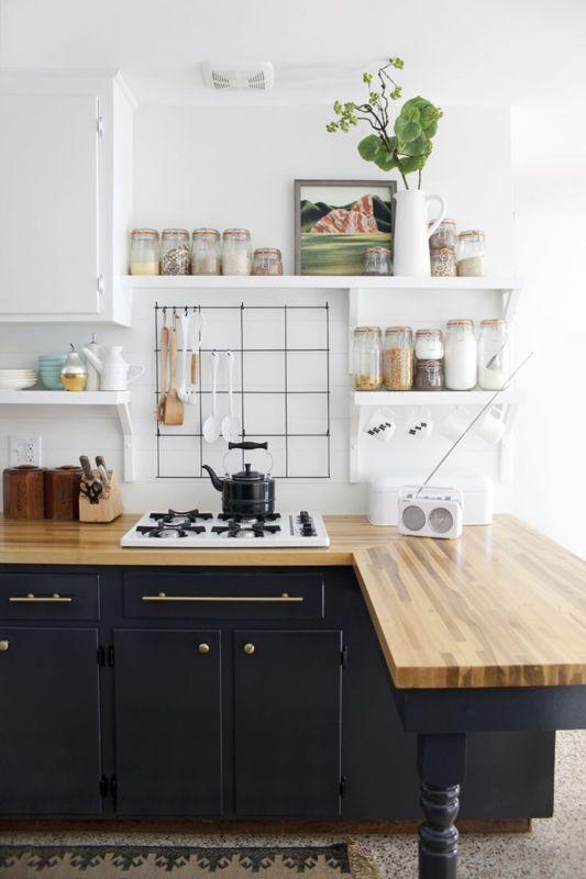 kitchen, grey floor tiles, black cabinet, wooden counter top, white wall, white floating shelves, white upper cabinet