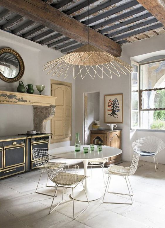 kitchen, grey floor tiles, grey wall, black cabinet with golden lines, wooden floating, yellow door, white wire steel chair, white round table, rattan pendant