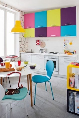 kitchen, grey floor tiles, white bottom cabinet, colorful upper cabinet, white backsplash, patterned wall, white round table, colorful chair