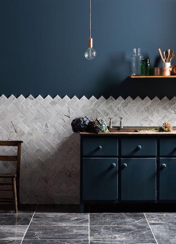 kitchen, grey marble floor, grey herringbone on half bottom of the wall, dark blue cabinet with wooden top, dark blue wall, bulb pendant, floating shelves
