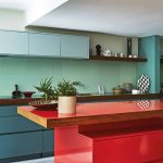 Kitchen, Grey Seamless Floor, Muted Green Bottom, Glossy Green Backsplash, Blue Floating Cabinet, Red Island