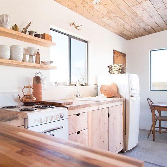 kitchen, grey wooden floor, wooden bottom cabinet, wooden kitchen top, wooden floating shelves, white stove, window, white fridge
