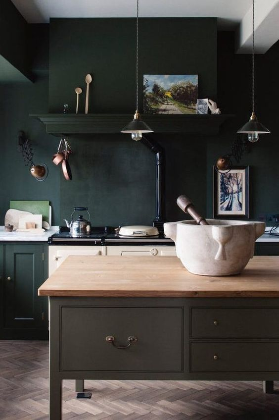 kitchen, herringbone brown floor tiles, dark green wall, dark green cabinet, white bottom cabinet, grey island with wooden top, pendants
