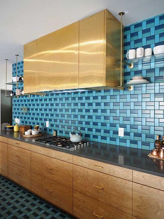 kitchen, patterned blue tiles on wall and floor, wooden cabinet, black kitchen top, golden upper cabinet, glass floating shelves
