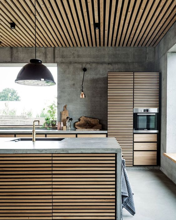 kitchen, seamless grey floor and wall, wooden slats island with grey top, wooden cabinet with grey top, wooden slats pantry, wooden slats ceiling, black pendant, golden sconces