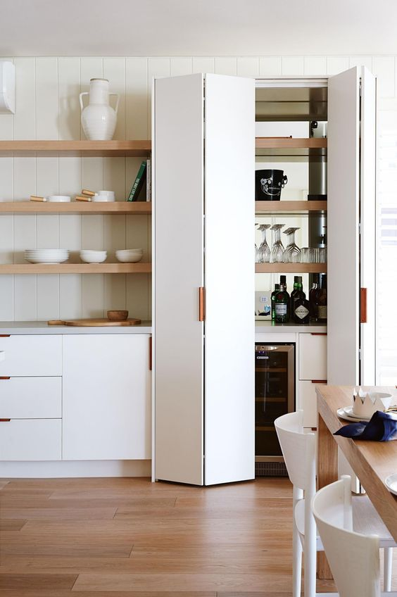 kitchen with wooden floor, white bottom cabinet, wooden open shelves, white folding door, wooden dining table, white chairs