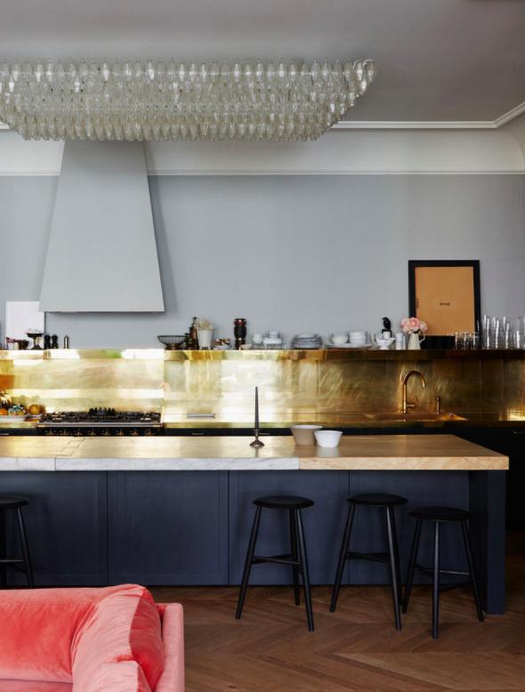 kitchen, wooden chevron floor, black islant with brown marble top, black cabinet, golden backsplash, golden open floatin gshelves, grey wall, crystal ceiling lamp