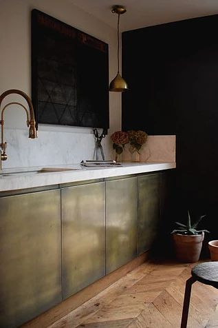 kitchen, wooden chevron floor, white marble backsplash, white wall, white marble top, washed out green cabinet, black floatin cabinet
