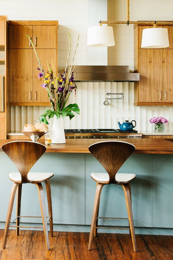 kitchen, wooden floor, blue island, wooden top, white jagged textued wall, wooden upper cabinet, white tiles wall, wooden stools, white pendants