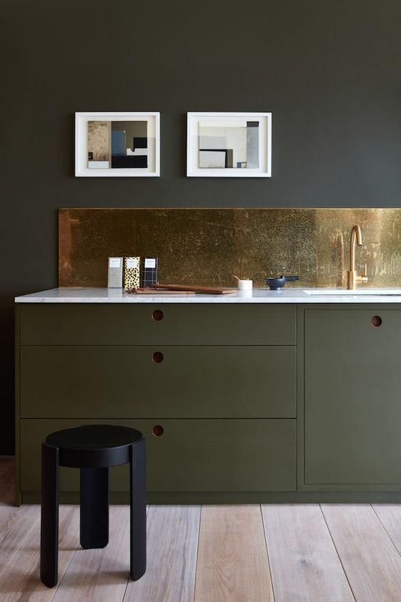 kitchen, wooden floor, dark green cabinet, dark wall, golden backsplash, white kitchen top