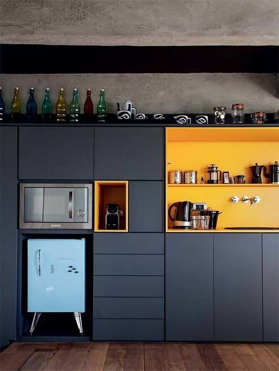 kitchen, wooden floor, grey cabinet and patnry, yellow shelves, grey wall, blue fridge