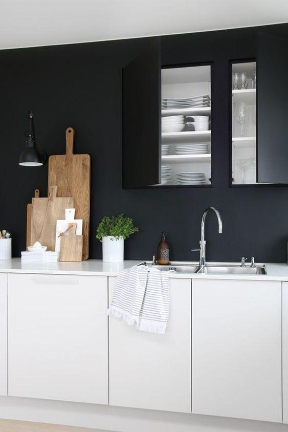 kitchen, wooden floor, white cabinet, black wall, black built in upper cabinet, black pendant, white top