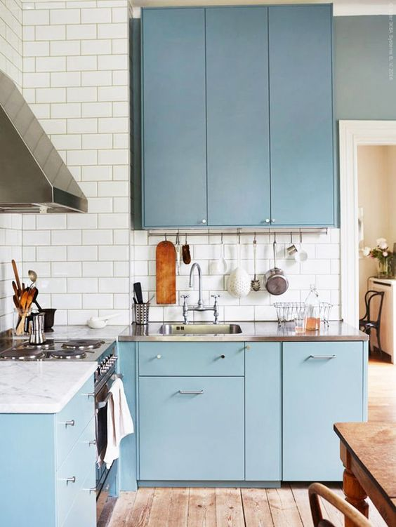 kitchen, wooden floor, white subway wall tiles, blue cabinet, steel kitchen top, white marble top, steel hood, wooden table set