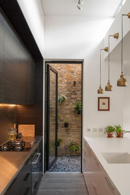 kitchen, wooden floor, white wall, white cabinet and counter, glass pendant, black cabinet upper and bottom with wooden kitchen top
