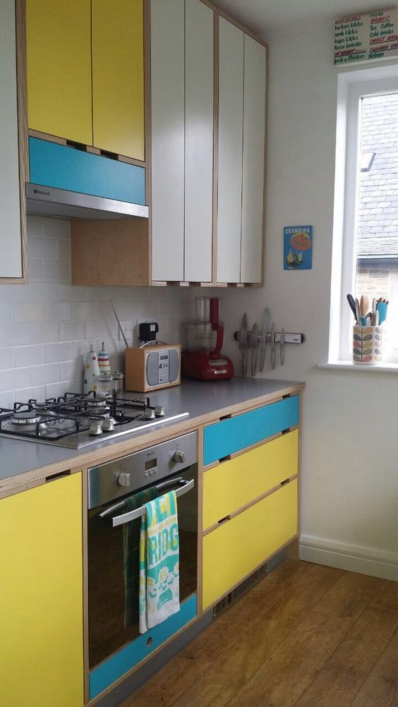 kitchen, wooden floor, white wall, white upper cabinet, yellow blue upper and bottom cabinet, grey kitchen top