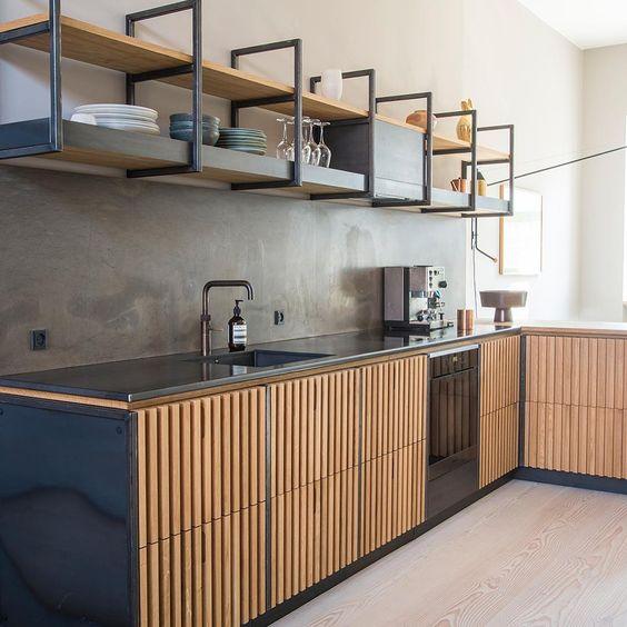 kitchen, wooden floor, wooden slats bottom cabinet, black top, seamless grey wall, floating shelves