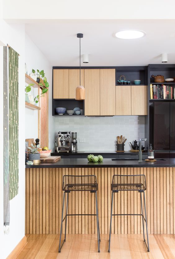 kitchen, wooden floor, wooden slats island with black top, wooden upper cabinet with black shelves, wooden pendant, white wall