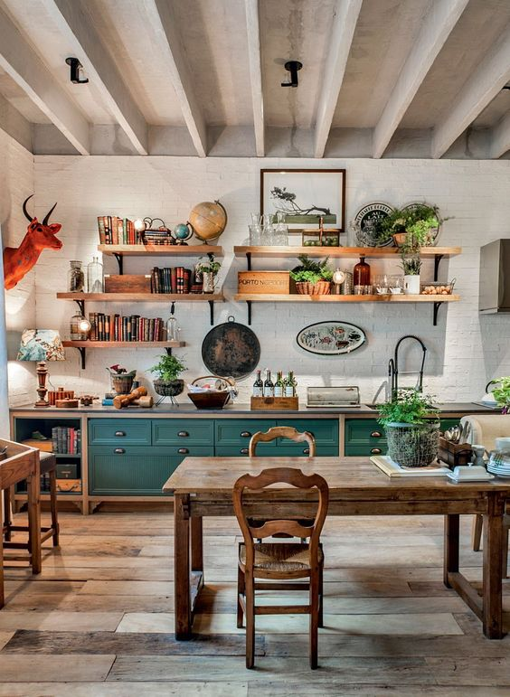 kitchen, wooden floor, wooden table, wooden chairs with rattan seat, green bottom cabinet, white open brick wall, wooden open floating shelves, white wooden striped ceiling