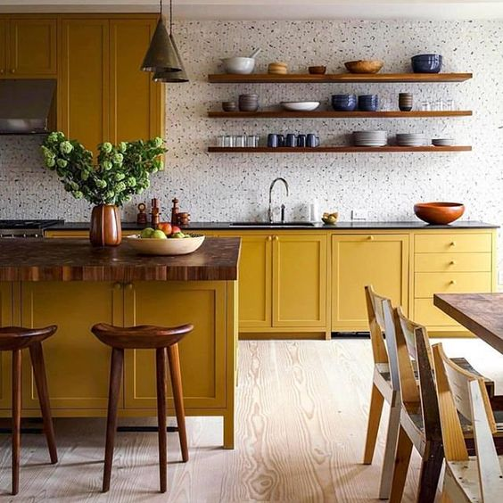 kitchen, wooden floor, yellow wooden cabinet with black top, yellow island with wooden top, wooden stools, wooden floating shelves, wooden dining table