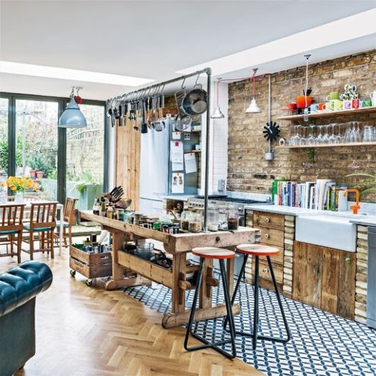 kitchen, wooden herringbone floor tiles, wooden island with metal rod, grey pendant, wooden boards bottom cabinet, floating sheles, dining table set