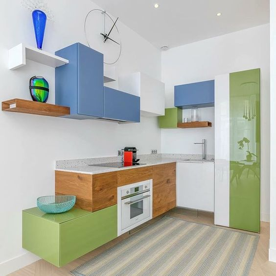 kitchen, wooden wall, striped rug, green wooden bottom cabinet, terazzo kitchen top, blue upper cabinet, floating shelves, white cabinet, white and green pantry