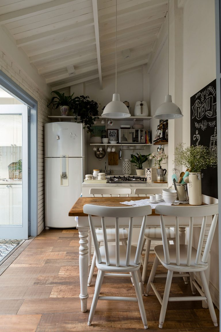 kithen, wooden floor, white wall, white kitchen with open shelves, white fridge, white pendants, wooden dining table with white chairs