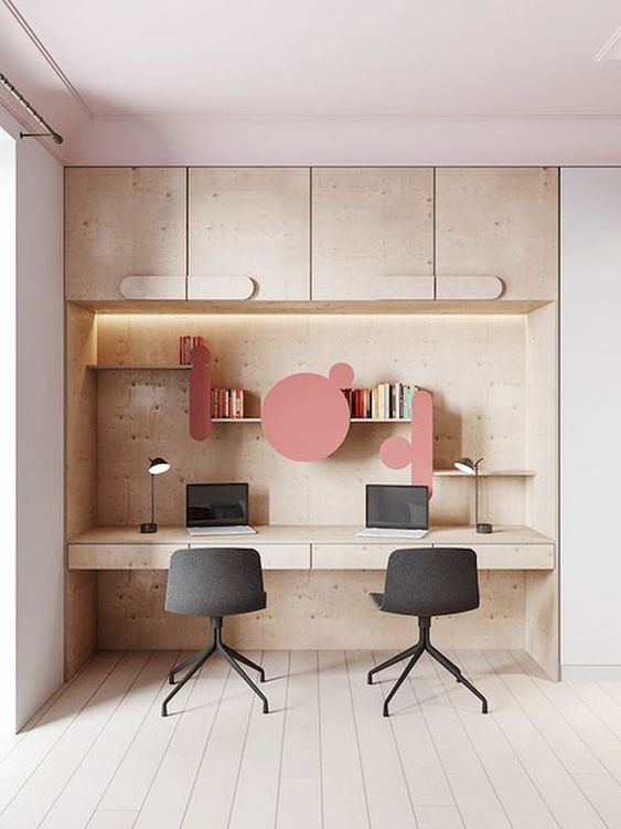 light brown wooden study in alcove, upper cabinet, shelves with pink accessories, floating table with drawers, black office chairs