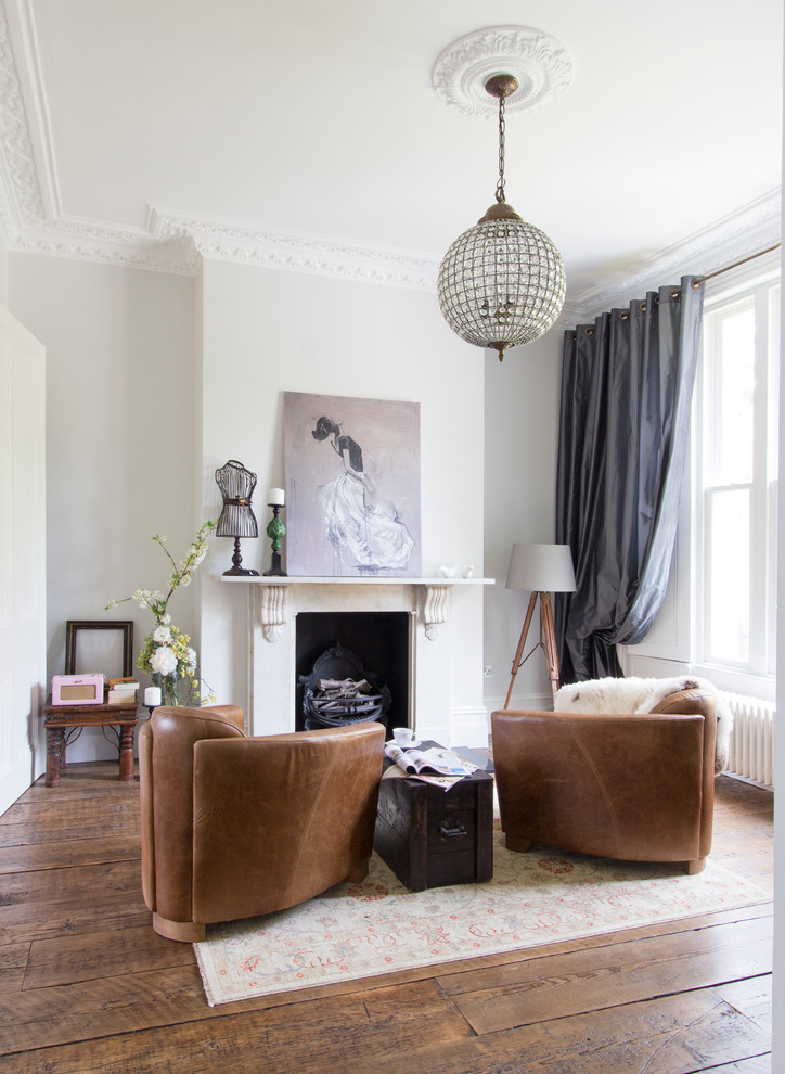 lighting floor lamps chandelier artwork fireplace gray drapes wooden floor area rug brown leatheres chairs coffee table white walls window white walls