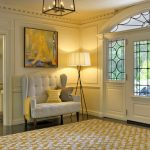 Lighting Floor Lamps Chandelier Glass Doors Window Yellow Patterned Area Rug Big Wingback Armchairs Tripod Floor Lamp Artwork Wall Trim Console Table Yellow And Gray Pillows