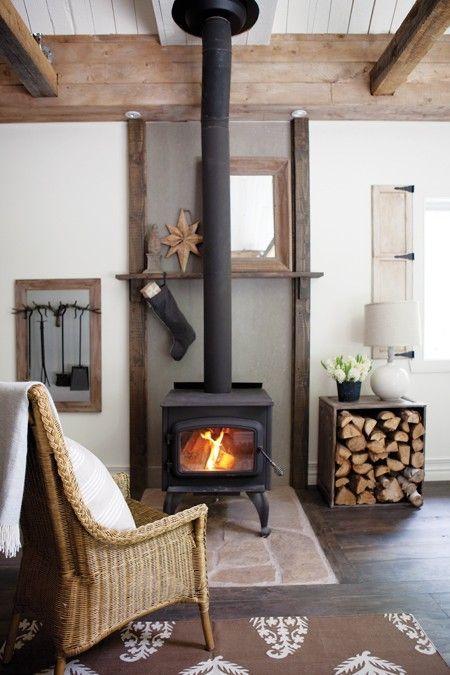 living room, dark wooden floor, natural stone floor tiles, black metal fireplace, white wall, white wooden ceiling, wooden beams,