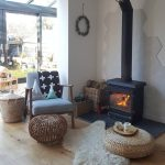 Living Room, Wooden Floor, Black Metal Fireplace, Rattan Ottomans, Wooden Chair With Blue Cushion, Ratan Baskets, White Wall,