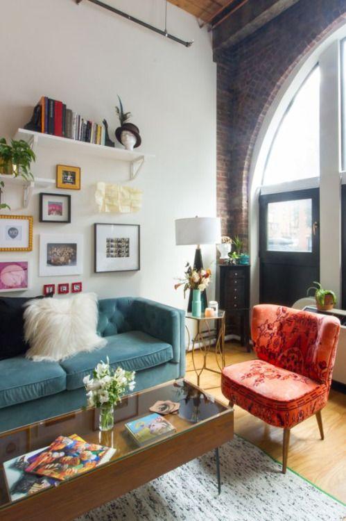 living room, wooden floor, white wall, brick wall, orange velvet chair, blue sofa, long coffee table, floating shelves, tall glass window