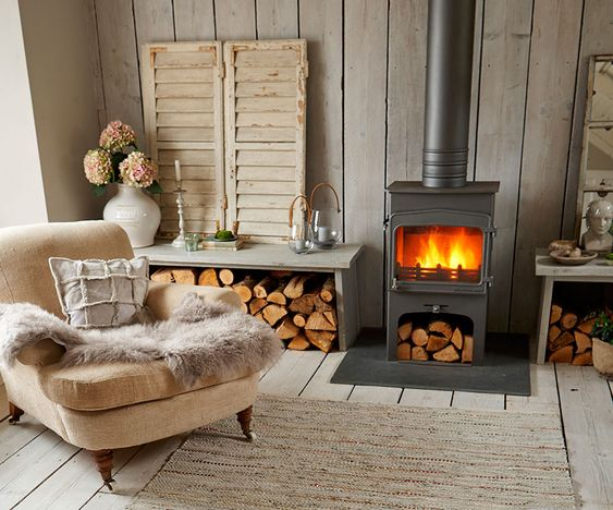 living room, wooden floor, wooden wall, grey metal fireplace, grey wooden table, beige lounge sofa with pillow