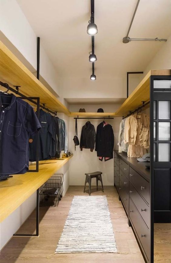 long space with yellows boards, rails to hang clothes, grey cabinet, wooden floor, rug, ceiling lamp