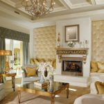 Luxurious Living Room Beige Tufted Wall Gray Curtain Glass Doors Fireplace Chandelier Coffee Table Sofa Gray Armchairs Gold Pillows Gold Table Lamp