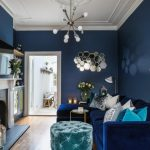 Luxurious Living Room Chandelier Blue Walls Honeycomb Wall Mirror Blue Velvet Sectional Sofa Pillows Blue Tufted Stools Round Cocktail Table Fireplace White Mantel Table Lamps