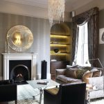 Luxurious Living Room Chandelier Round Wall Mirror Black Fireplace Black Armchairs Shelves Small Floor Lamp Square Coffee Table Area Rug Sofa Pillows
