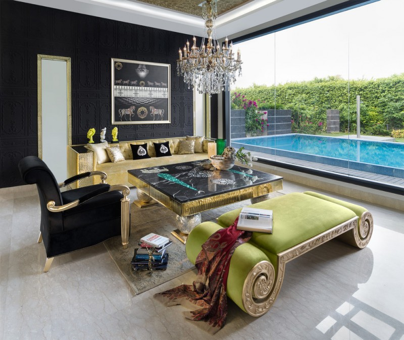 luxurious living room gold sofa black and gold coffee table green bench black armchair crystal chandelier wide glass window artwork black walls area rug