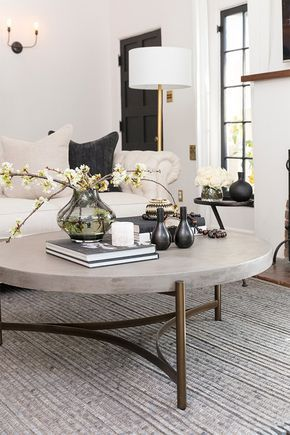 marble coffee table with brown legs, grey rug, white sofa, white floor lamp, white wall