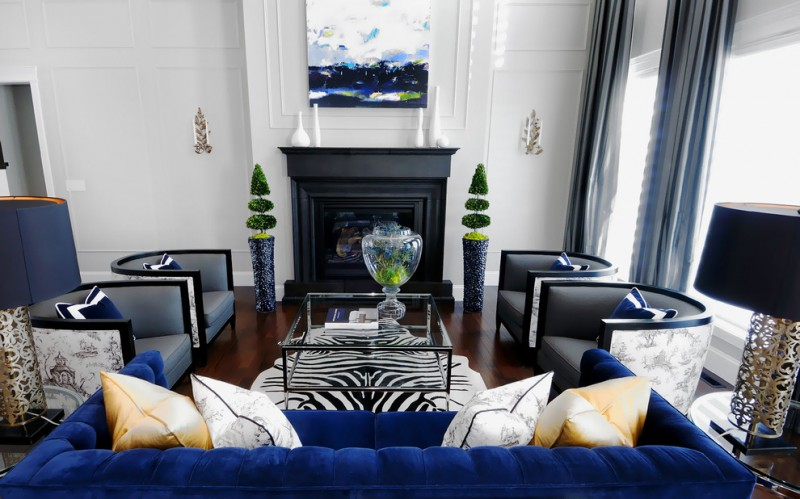 modern blue couch black fireplace artwork blue curtains gray armchairs glass coffee table zebra rug wooden floor window table lamps white wall sconces pillows