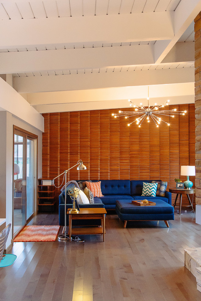 modern blue couch brown accent wall chandelier wooden side tablw blue ottoman industrial chrome floor lamp table almp sliding glass doors colorful pillows mat