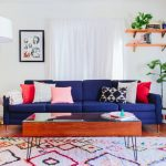 Modern Blue Couch Colorful Pillows Colorful Rug Glass Coffee Table Wall Mounted Shelves Wooden Floor White Floor Lamp Indoor Plant White Curtains Artwork