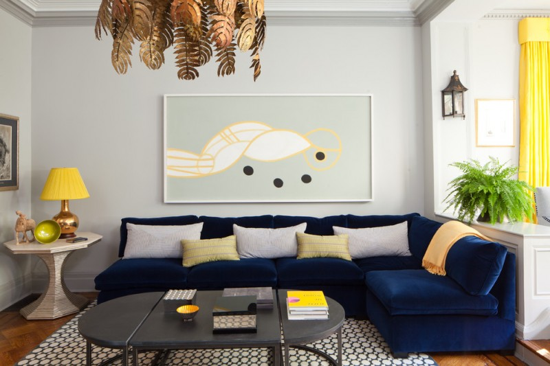 modern blue couch leaf chandelier pillows round side table yellow and gold table lamp black coffee table area rug artwork gray walls wall sconce yellow curtain